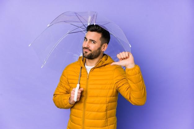 Jeune bel homme tenant un parapluie isolé se sent fier et confiant, exemple à suivre.