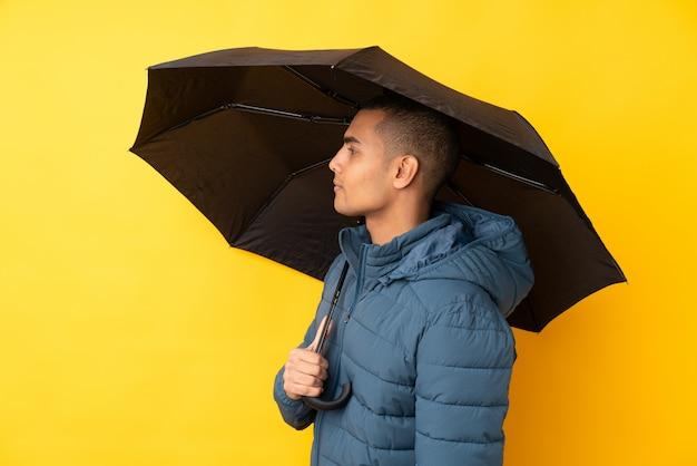 Jeune bel homme tenant un parapluie sur un mur jaune isolé avec une expression heureuse