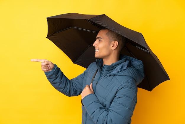 Jeune bel homme tenant un parapluie sur un mur jaune isolé pointant vers le côté pour présenter un produit