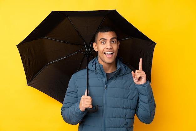 Jeune bel homme tenant un parapluie sur un mur jaune isolé pointant vers le haut une excellente idée