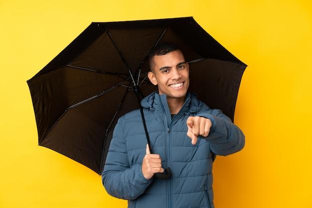 Jeune bel homme tenant un parapluie sur le mur jaune isolé pointe le doigt vers vous avec une expression confiante
