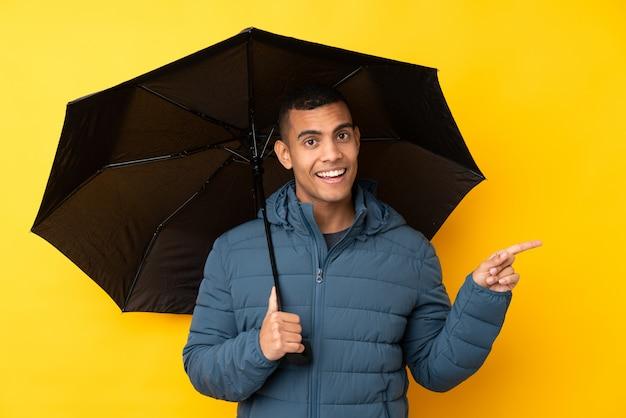 Jeune bel homme tenant un parapluie sur un mur jaune isolé surpris et pointant le doigt sur le côté