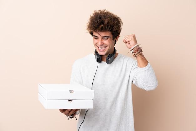Jeune bel homme tenant une pizza sur un mur isolé célébrant une victoire