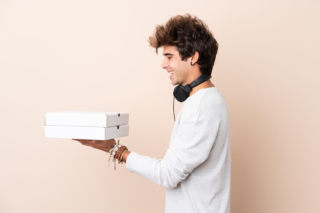 Jeune bel homme tenant une pizza sur un mur isolé avec une expression heureuse