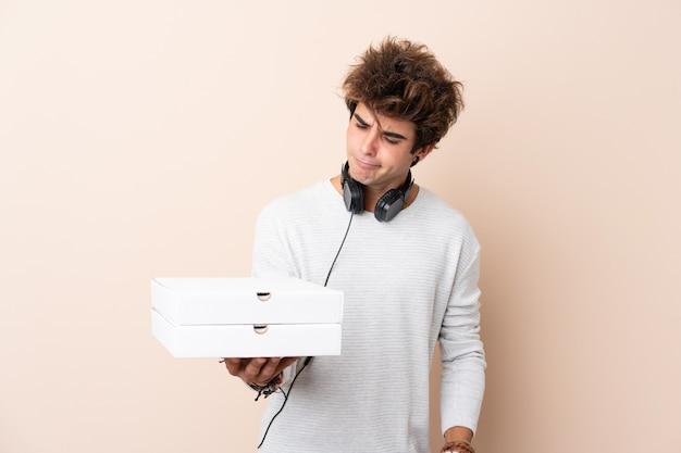 Jeune bel homme tenant une pizza sur un mur isolé avec une expression triste