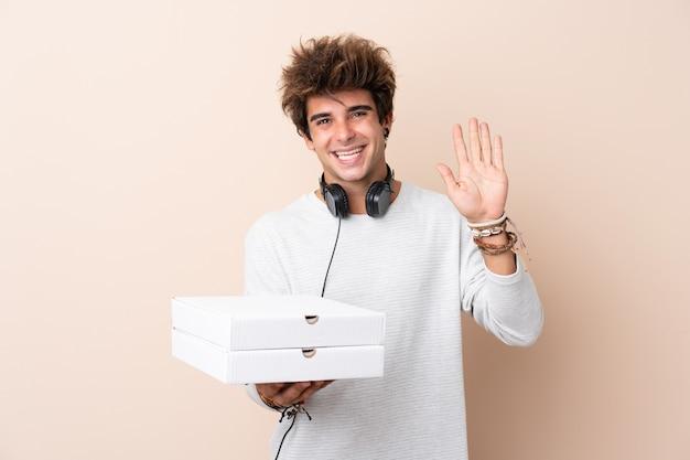 Jeune bel homme tenant une pizza sur un mur isolé saluant avec la main avec une expression heureuse