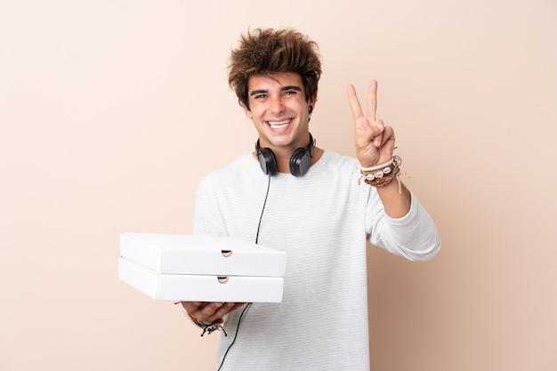 Jeune bel homme tenant une pizza sur un mur isolé, souriant et montrant le signe de la victoire