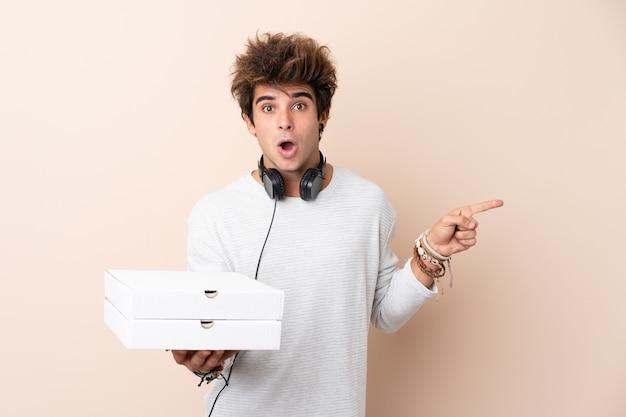 Jeune bel homme tenant une pizza sur un mur isolé surpris et pointant le côté
