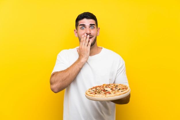 Jeune bel homme tenant une pizza sur un mur jaune avec une expression faciale surprise