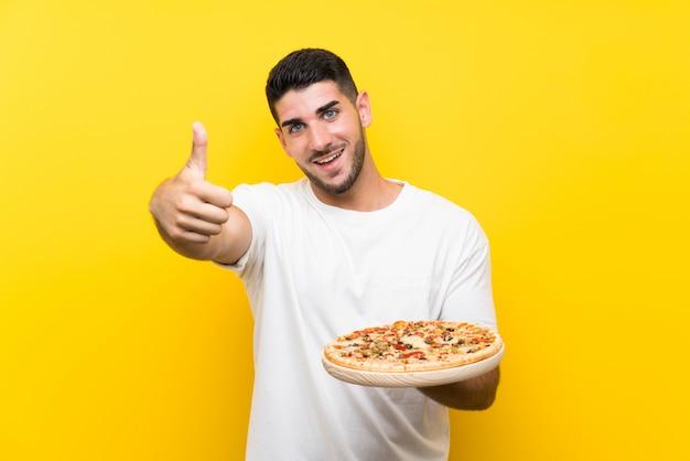 Jeune bel homme tenant une pizza sur un mur jaune avec le pouce levé parce que quelque chose de bien est arrivé