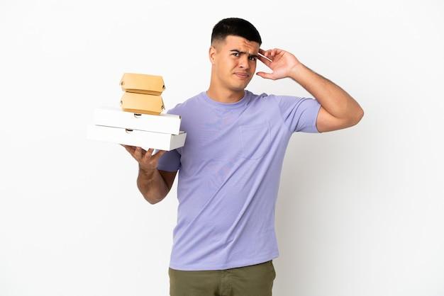 Jeune bel homme tenant des pizzas et des hamburgers sur fond blanc isolé ayant des doutes