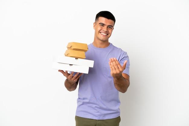 Jeune bel homme tenant des pizzas et des hamburgers sur fond blanc isolé invitant à venir avec la main. heureux que tu sois venu