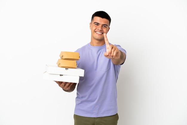 Jeune bel homme tenant des pizzas et des hamburgers sur fond blanc isolé montrant et levant un doigt