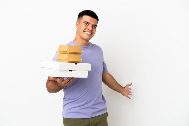 Jeune bel homme tenant des pizzas et des hamburgers sur fond blanc isolé tendant les mains sur le côté pour inviter à venir