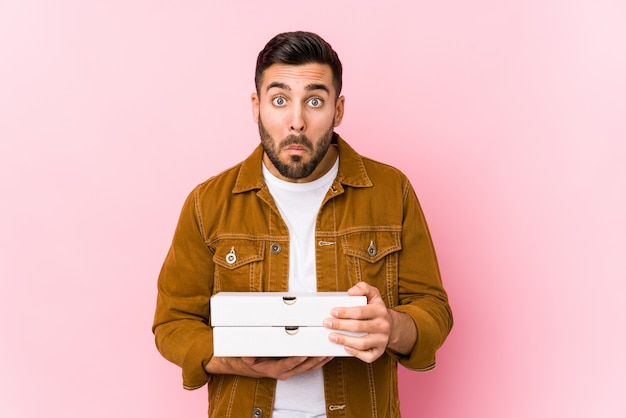 Jeune bel homme tenant des pizzas hausse les épaules et les yeux ouverts confus.