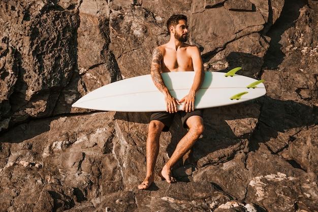 Jeune bel homme tenant la planche de surf près de pierres