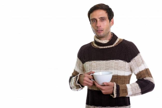 Jeune bel homme tenant une tasse de café à deux mains