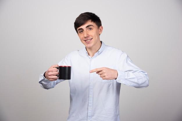 Jeune bel homme tenant une tasse de thé sur un mur gris.