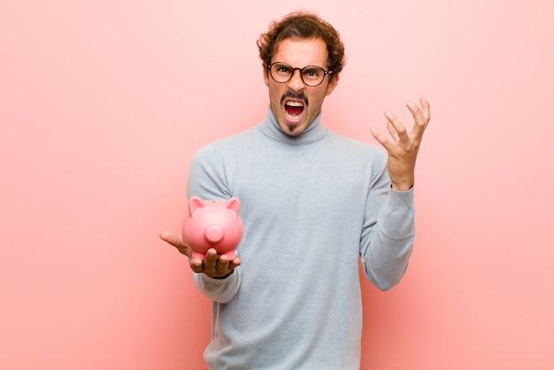 Jeune bel homme avec une tirelire contre le mur plat rose