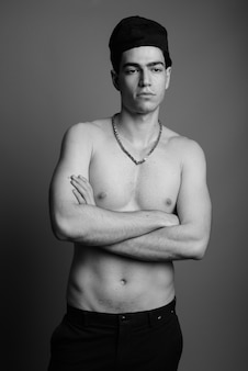 Jeune bel homme torse nu contre le mur gris