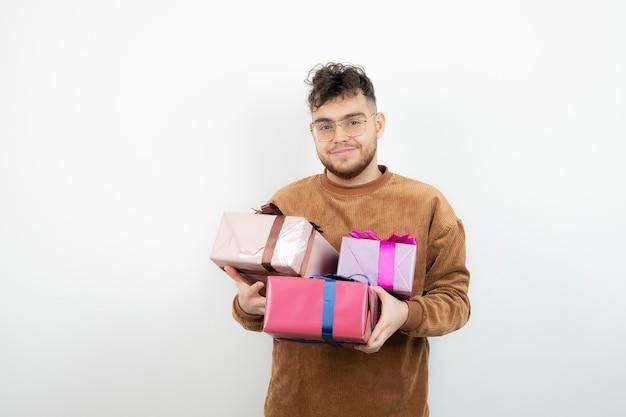 Jeune bel homme transportant de nombreux coffrets cadeaux.