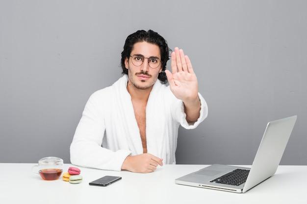 Jeune bel homme travaillant après une douche debout avec la main tendue montrant le panneau d'arrêt, vous empêchant.