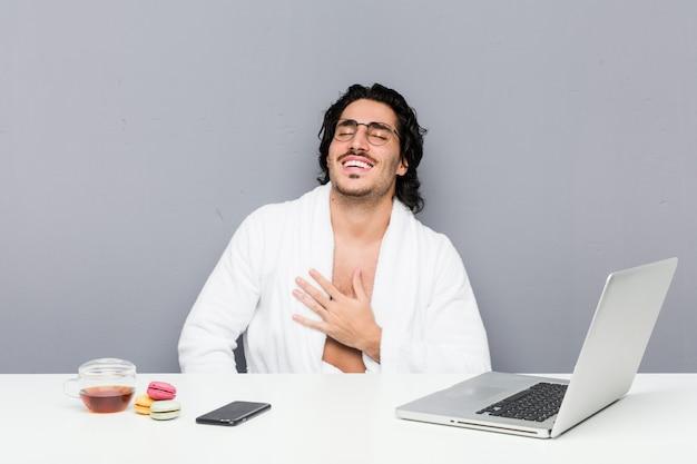 Jeune bel homme travaillant après une douche éclate de rire bruyamment en gardant la main sur la poitrine