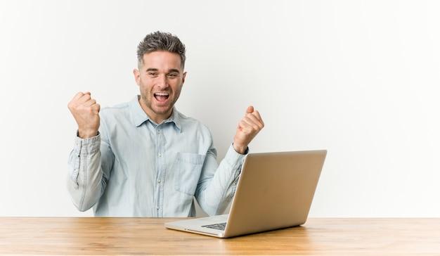 Jeune bel homme travaillant avec son ordinateur portable applaudissant insouciant et excité. concept de victoire.