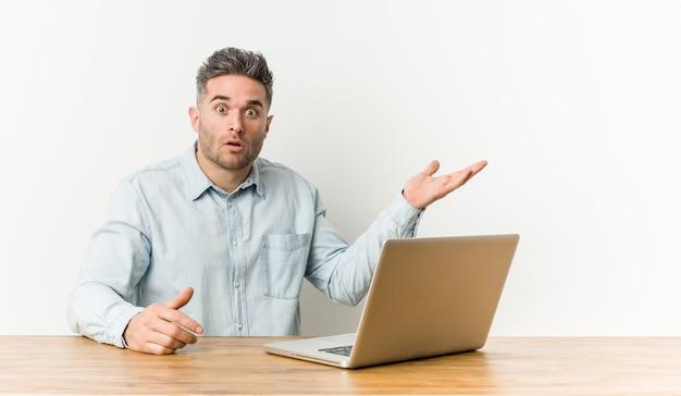 Jeune bel homme travaillant avec son ordinateur portable impressionné tenant l'espace copie sur la paume.