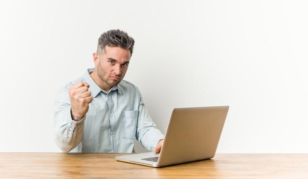 Jeune bel homme travaillant avec son ordinateur portable montrant le poing à la caméra, expression faciale agressive.