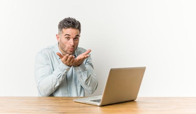 Jeune bel homme travaillant avec son ordinateur portable pliant les lèvres et tenant les paumes pour envoyer un baiser aérien.