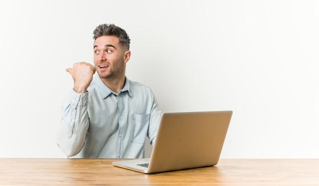 Jeune bel homme travaillant avec son ordinateur portable pointe avec le doigt du pouce, rire et insouciant.