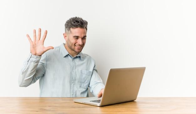 Jeune bel homme travaillant avec son ordinateur portable souriant gai montrant le numéro cinq avec les doigts.