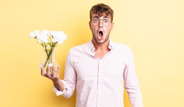 Jeune bel homme très choqué ou surpris. concept de fleurs