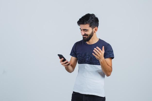 Jeune bel homme utilisant un téléphone