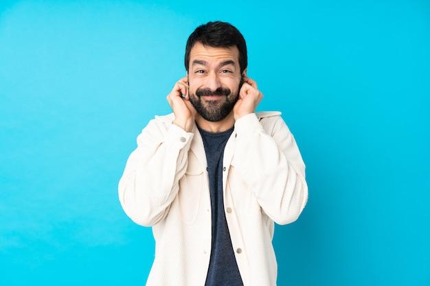 Jeune bel homme avec veste en velours côtelé blanc sur bleu frustré et couvrant les oreilles