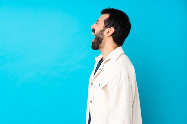 Jeune bel homme avec veste en velours côtelé blanc sur bleu rire en position latérale