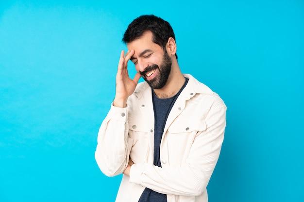 Jeune bel homme avec une veste en velours côtelé blanc sur bleu rire