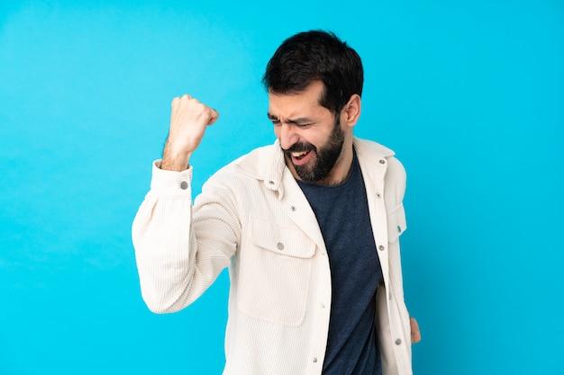 Jeune bel homme avec une veste en velours côtelé blanc célébrant une victoire
