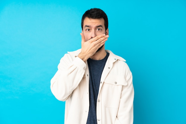Jeune bel homme avec une veste en velours côtelé blanc couvrant la bouche avec les mains