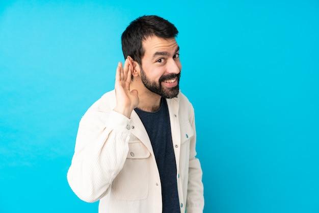 Jeune bel homme avec une veste en velours côtelé blanc écouter quelque chose en mettant la main sur l'oreille