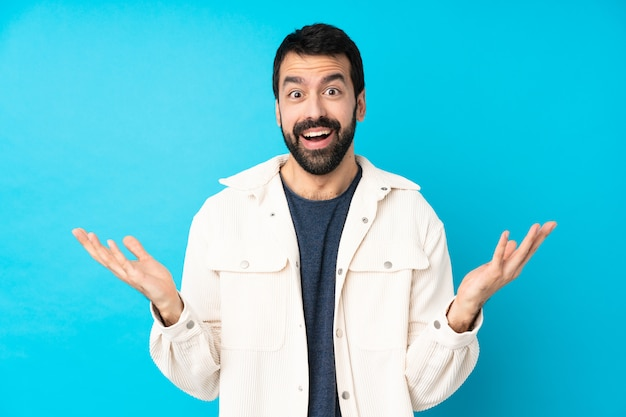 Jeune bel homme avec une veste en velours côtelé blanc avec une expression faciale choquée