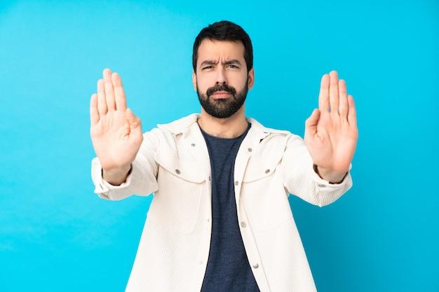 Jeune bel homme avec une veste en velours côtelé blanc faisant un geste d'arrêt et déçu