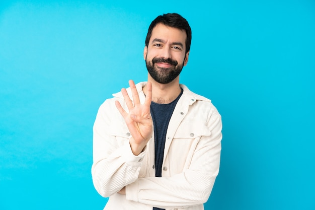 Jeune bel homme avec une veste en velours côtelé blanc heureux et en comptant quatre avec les doigts