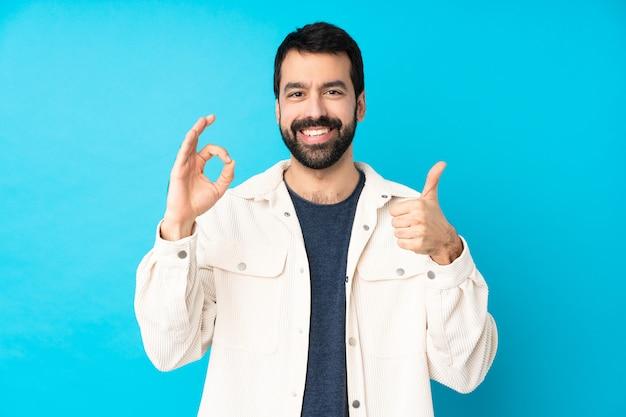 Jeune bel homme avec une veste en velours côtelé blanc montrant le signe ok et le geste du pouce vers le haut