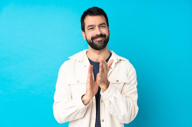 Jeune bel homme avec veste en velours côtelé blanc sur mur bleu isolé applaudissant après présentation dans une conférence
