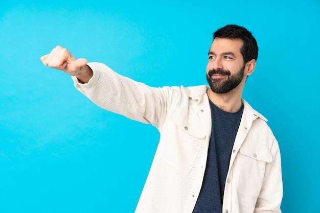 Jeune bel homme avec veste en velours côtelé blanc sur mur bleu isolé donnant un coup de pouce geste