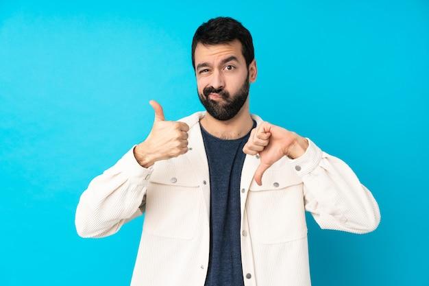 Jeune bel homme avec une veste en velours côtelé blanc sur un mur bleu isolé faisant signe bon-mauvais. indécis entre oui ou non