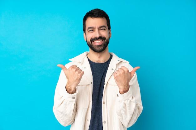 Jeune bel homme avec une veste en velours côtelé blanc sur un mur bleu isolé avec les pouces vers le haut de geste et souriant