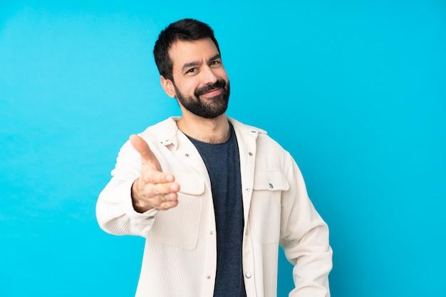 Jeune bel homme avec veste en velours côtelé blanc sur mur bleu isolé se serrant la main pour fermer une bonne affaire